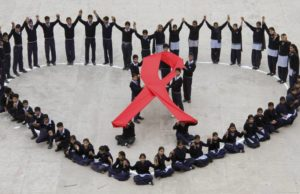 Students make a formation in the shape of a heart and a red ribbon during a HIV/AIDS awareness campaign on Valentine's Day in the northern Indian city of Chandigarh